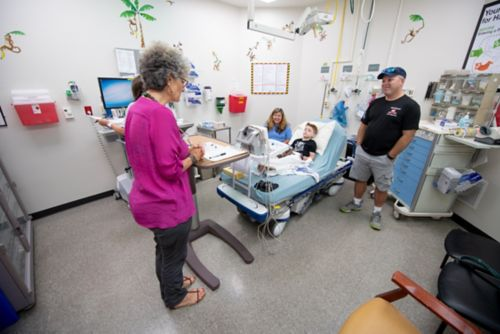 An anesthesiologist meets with a family before the patient receives general anesthesia for a procedure.