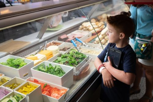 Cancer survivors who develop healthy eating habits can reduce the risk of obesity and may reduce the risk of some types of adult cancers. Young patient reviews options in a deli case.