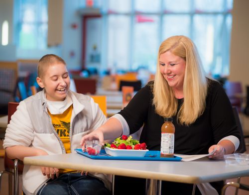 Clinical nutritionist reviews healthy food choices with pediatric cancer patient