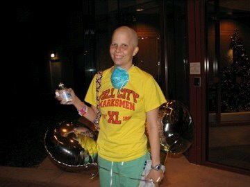 A patient standing in a yellow shirt, holding balloons and a drink bottle, with a blue mask draped around their neck.