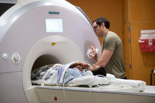 Paciente de cáncer infantil ubicada para realizarse una exploración por IRM del cuerpo completo con el papá y dos técnicos en IRM junto a ella.