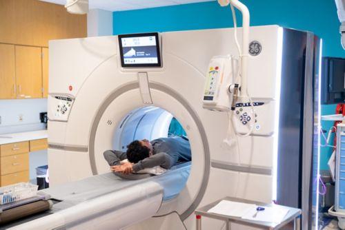 Un técnico en TC administra un contraste a un paciente con cáncer pediátrico, quien está acompañada por su madre.