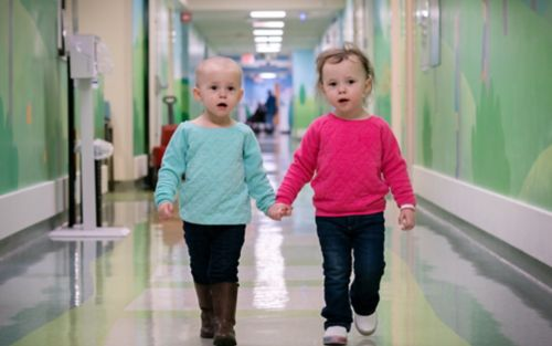 Two young patients walking down a hallway toward the camera