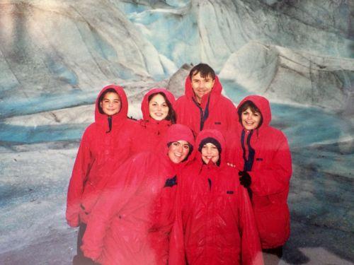 Familia de pie frente a un muro de hielo con chaquetas rojas iguales.