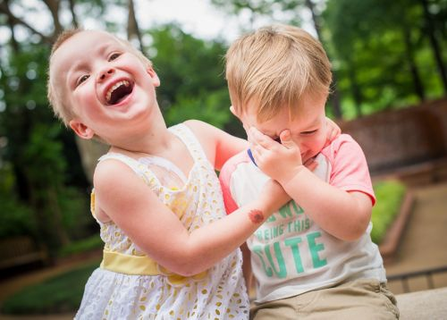 Young pediatric cancer patient plays with her brother outside