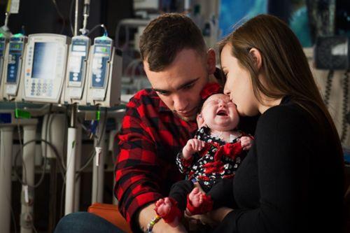 Une famille réconforte un nourrisson en pleurs dans une chambre d'hôpital.