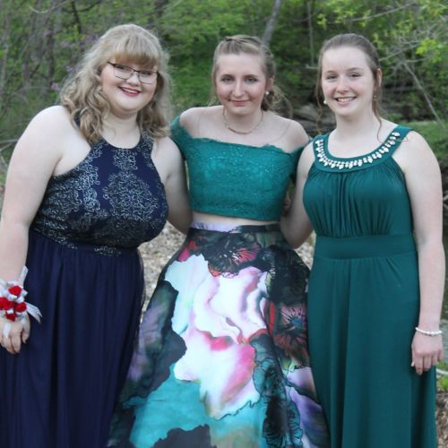 Three people in dresses before prom.