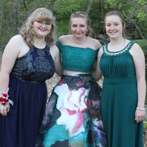 Tres adolescentes con sus vestidos antes del baile de graduación.