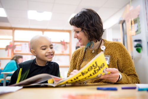 Teacher smiles at a child with cancer as they read a book.