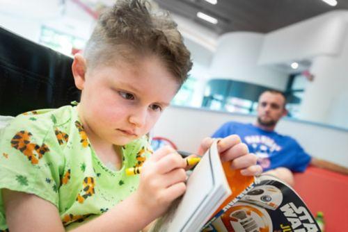 ¿Cómo hablarle a su hijo sobre el COVID-19? Esta foto muestra a un padre mirando a su hijo mientras colorea en la sala de espera de un hospital.