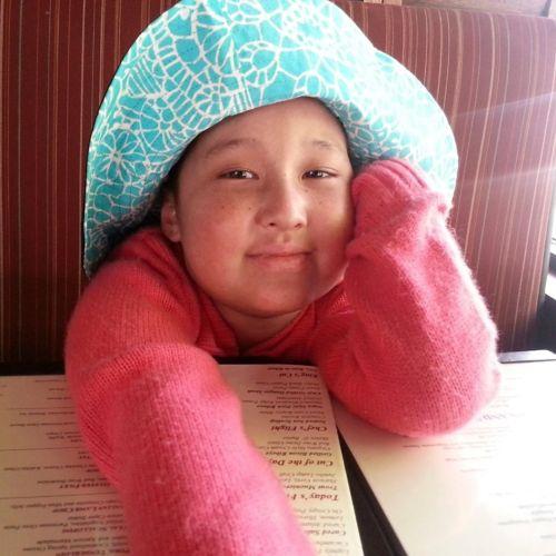 Paciente apoyada sobre una mesa con un suéter rosa y un sombrero azul