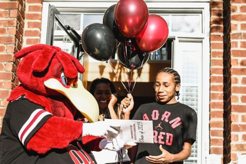 MJ receives his acceptance letter to the University of South Carolina by the costumed mascot of the college.