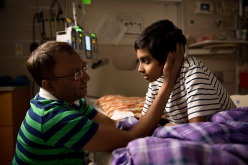 Father of a pediatric cancer patient, talks to his son in the hospital room