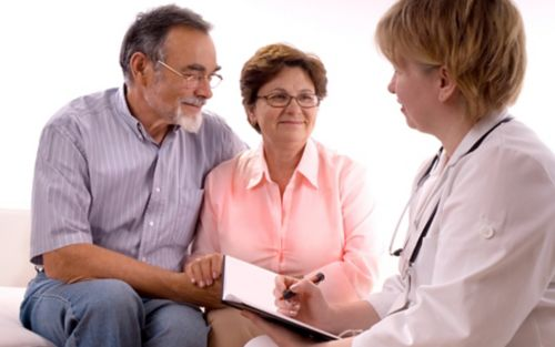 Doctor speaking to older couple