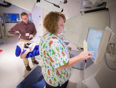 Un radioterapeuta prepara la computadora para un tratamiento oncológico pediátrico con radiación junto con otro radioterapeuta y un paciente en el fondo.
