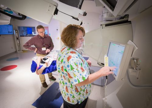 Radiation therapist prepares the computer for a pediatric cancer radiation treatment with another radiation therapist and a patient in the background.