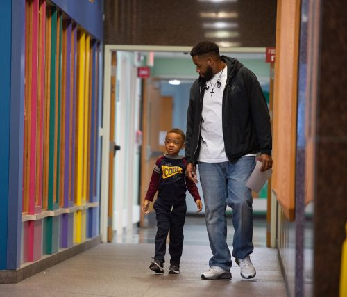 It can be helpful to bring copies of important documents such as your child's birth certificate, Social Security numbers for the patient and parents or guardians, insurance documents, copies of any custody papers, and other legal papers that pertain to the patient's health. This photo depicts a father and son walking down a hospital hallway.