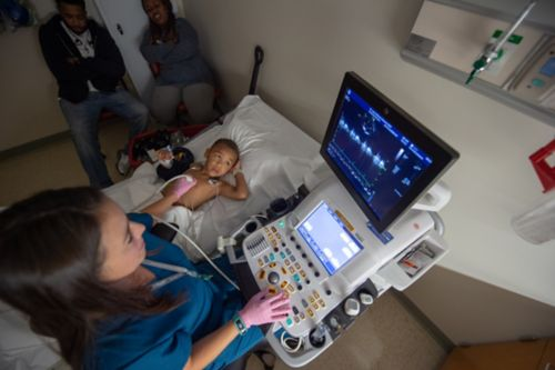 Heart tests such as an echocardiogram (echo) may be used to detect early signs of heart disease. In this image, a young survivor of childhood cancer is having an echo performed by a provider.
