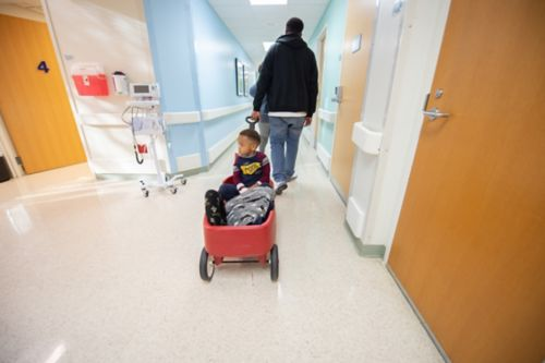 A doctor may wait until all the test results are back before discussing the information. Depending on the type of test, it may take a few hours to a few weeks before the results are ready. In this photo, a father pulls his son through a hospital hallway in a red wagon.