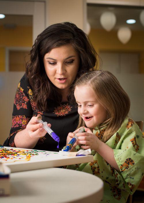 Joven paciente con cáncer pediátrico pinta con jeringas acompañada por una miembro del personal del hospital