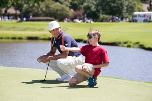 Young rhabdomyosarcoma patient kneels, talking with a golfer at a tournament