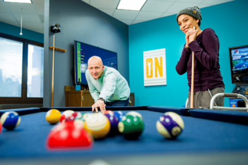 Two teen cancer patients play a game of pool together.