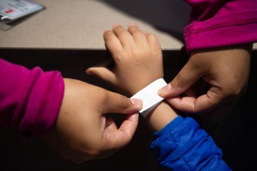 Cuando su hijo tiene cáncer, empacar para una hospitalización puede ser abrumador. La imagen muestra la mano de una empleada encargada de la admisión que le coloca una pulsera de hospital a un paciente de cáncer infantil.