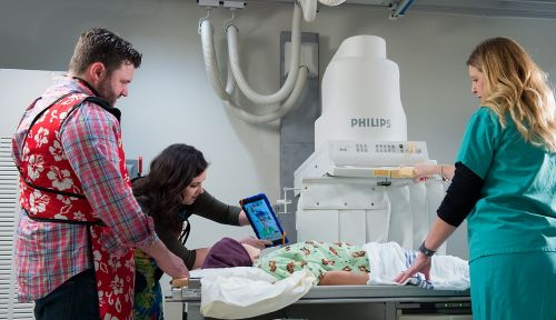 Le patient atteint d'un cancer pédiatrique est allongé sur une table tandis que le spécialiste de l'enfance lui tend un iPad et pendant que le technicien en radiographie positionne la machine pour une acquisition abdominale.