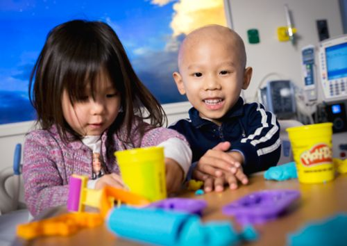 Pediatric cancer patient plays with modeling clay in a hospital bed with his sister.