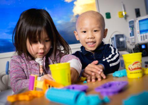 Un enfant atteint d'un cancer joue avec de la pâte à modeler dans un lit d'hôpital avec sa sœur.