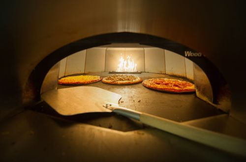 Pizza oven with three pizzas cooking by a wood fire