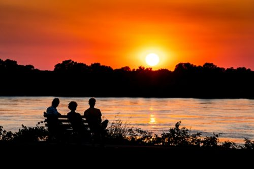 A family sitting on a bench beside the river watching the sunset.