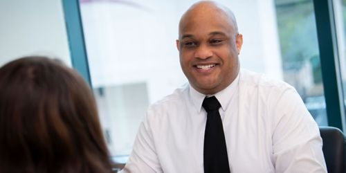 photo of smiling man in dress shirt and tie