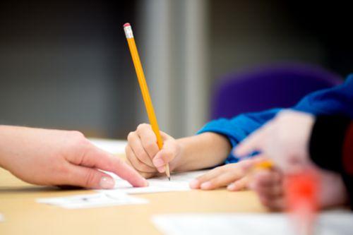 Mano de una maestra señalando un lugar en un papel y mano de un paciente de cáncer sosteniendo un lápiz.