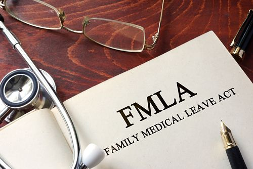 An open book on a table next to a stethoscope and a pair of glasses. The book says FMLA Family Medical Leave Act.