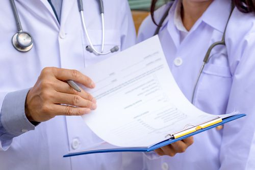 Dos miembros del equipo de atención médica sostienen un informe de patología