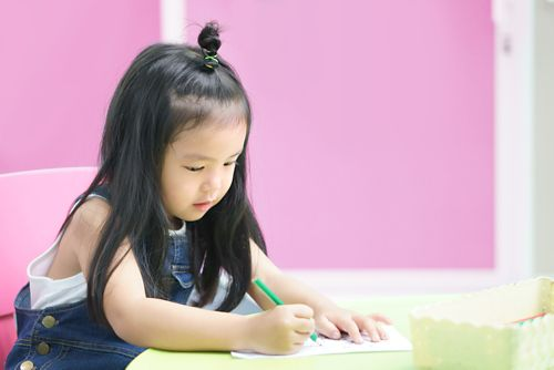 A young student writing on a sheet of paper.