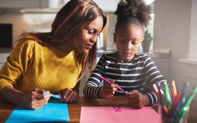 A mother and daughter working on craft projects.
