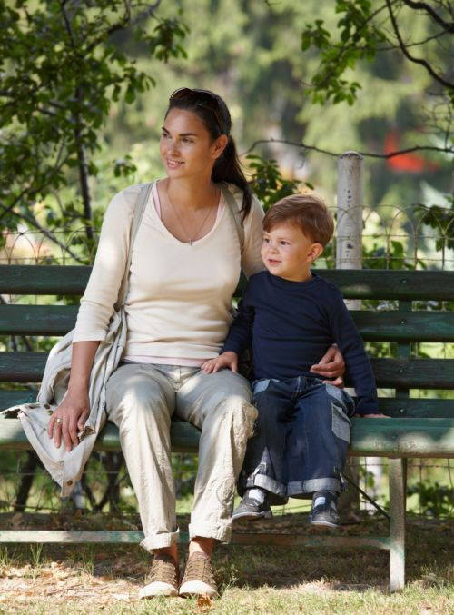 A mother and young son seated on a bench outside.