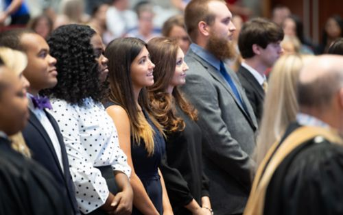 Graduate school students standing at event