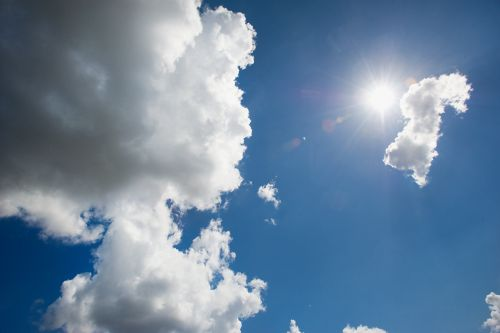 This picture shows a blue sky with a few white clouds and a beaming sun.