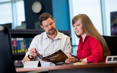 Faculty member and student looking at publication