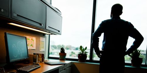 Image of man looking out window with his back to the camera