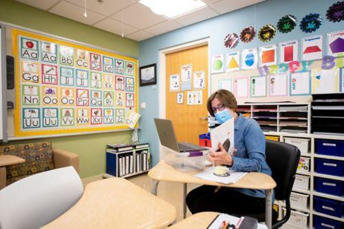Teacher sits in a St. Jude classroom
