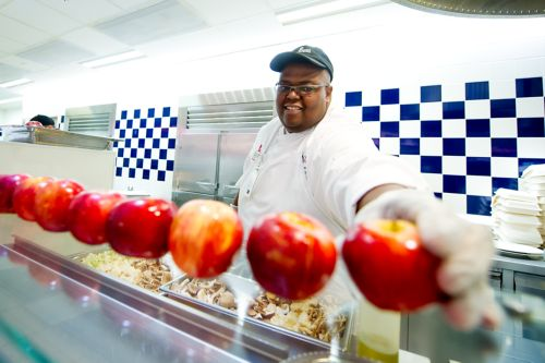Cafeteria worker places apples on a counter