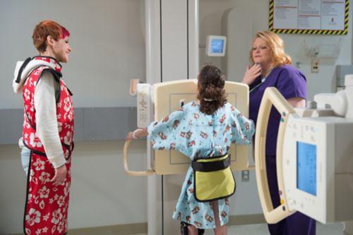 Le patient atteint d'un cancer pédiatrique est installé par un technicien en radiographie. Sa mère qui l'accompagne a revêtu un tablier de plomb.